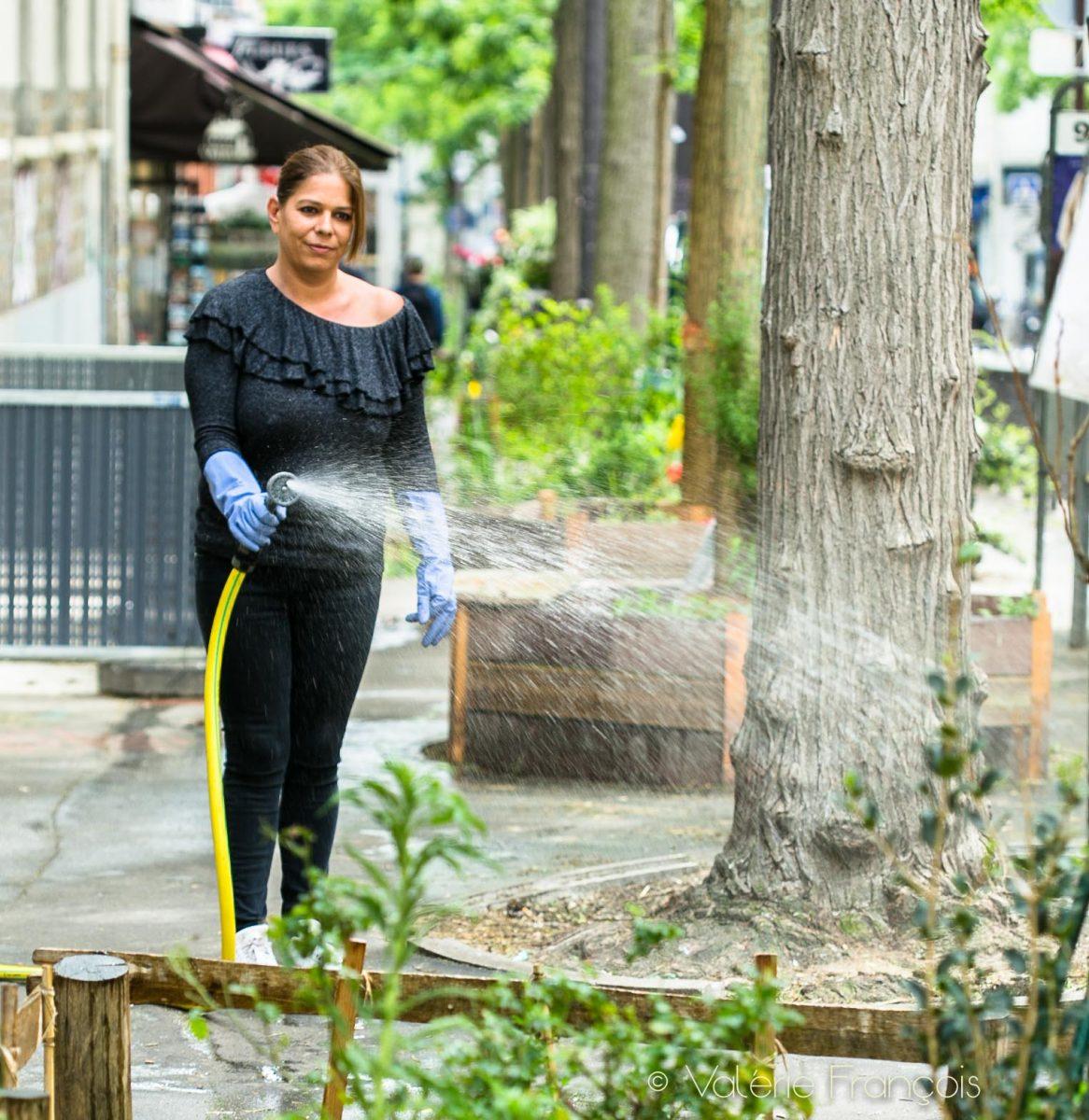 Végétalisation de Paris : Frédérique arrose les pieds d'arbre végétalisés rue des Pyrénées